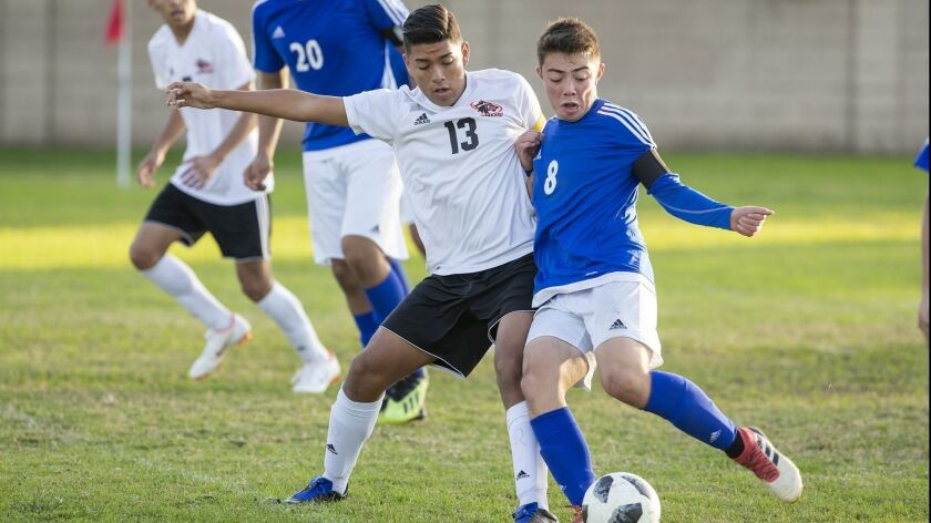 Los Amigos' Alfonso Montano battles for a ball against La Quinta's Ken Hatfield during a Garden Grov