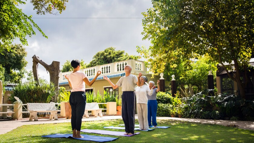 An instructor performs yoga with seniors at a retirement community. Such complexes can't block in-home caregivers by requiring that residents be capable of living independently.