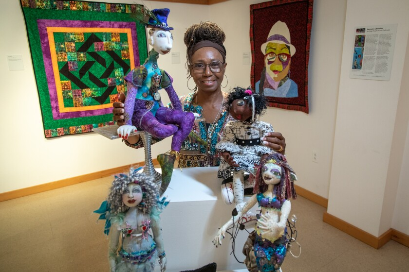 """Textile artist Gloria Hazel poses with some of her fabric dolls featured in """"Expressive Liberations"""" at Liberty Station."""