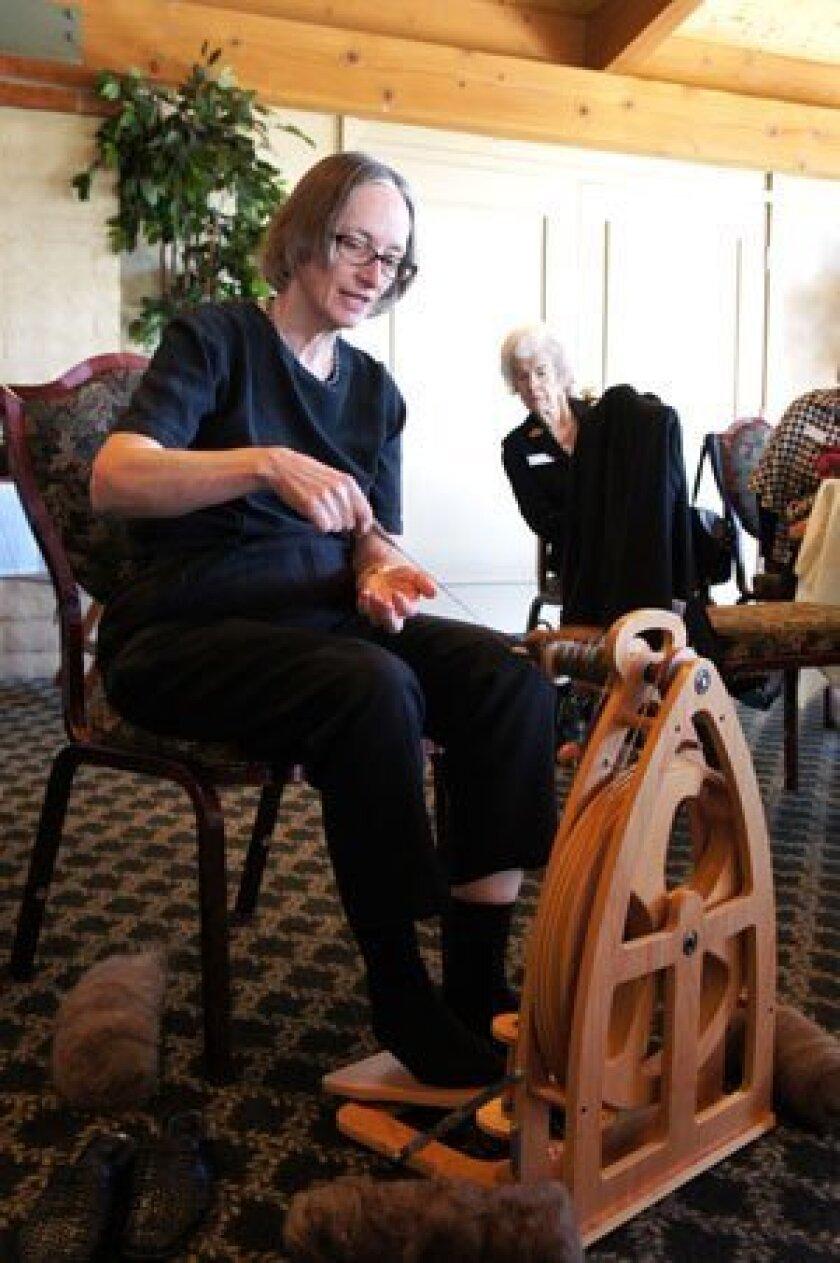 Beth Jurecki, weaving wool into yarn; Norada Wilkey looking on.