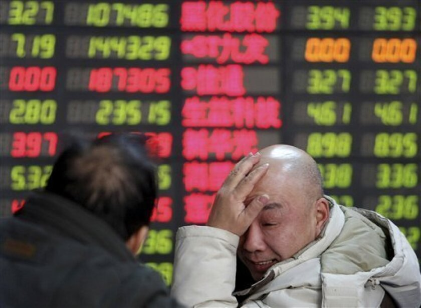 An investor reacts as he looks at the stock price monitor at a private securities company Tuesday, Jan. 13, 2009 in Shanghai, China. Chinese shares fell Tuesday on unease about a bleak outlook for corporate profits and declines on Wall Street and elsewhere in Asia. The benchmark Shanghai Composite