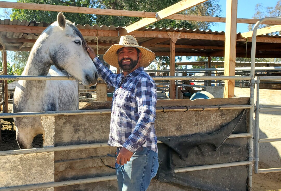 A man in a straw hat pets a white and gray horse.