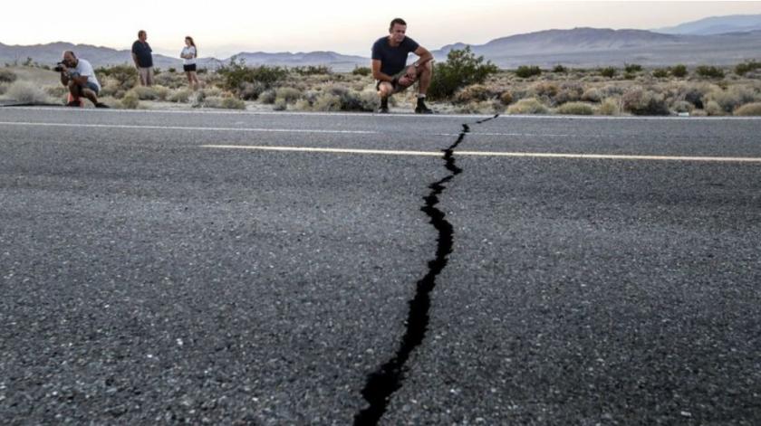 Heath Williamson, de Australia, observa una grieta a lo largo de la Autopista 178, entre Ridgecrest y Trona. (Irfan Khan / Los Angeles Times)