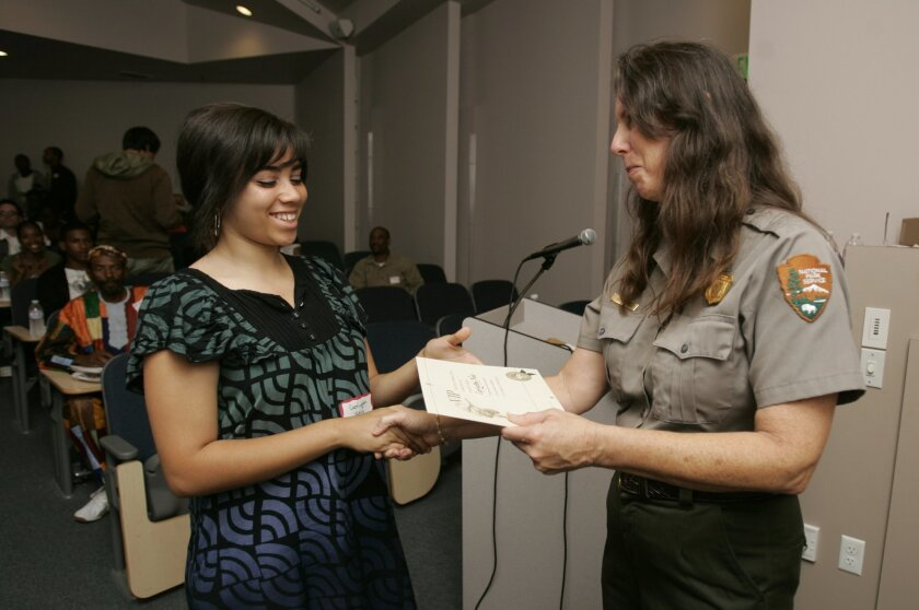 Carrington Novo, 15, a sophomore from Steele Canyon High School who will participate in a climate-change study this summer at Glacier National Park in Montana, receives a certificate as a sworn official National Park staff member from ranger Susan Steel.