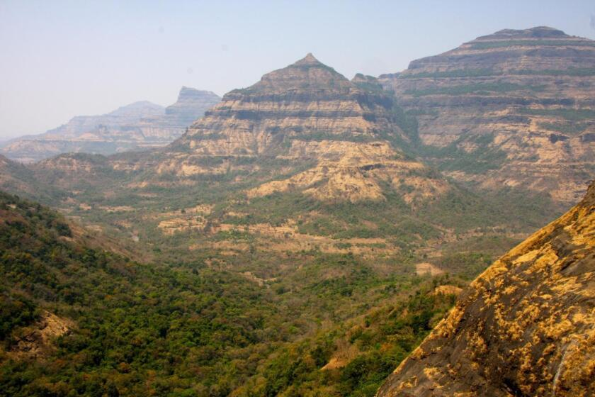 These are layered lava flows of the Deccan Traps east of Mumbai, India. Scientists think that volcanic activity here may have contributed to the extinction of the dinosaurs some 66 million years ago.