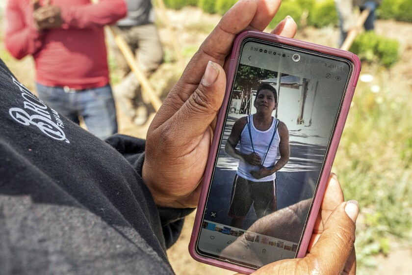 A worker, who declined to be named, looks at a photo of Sebastian Francisco Perez who died last weekend while working in an extreme heat wave, Thursday, July 1, 2021, near St. Paul, Ore. (AP Photo/Nathan Howard)