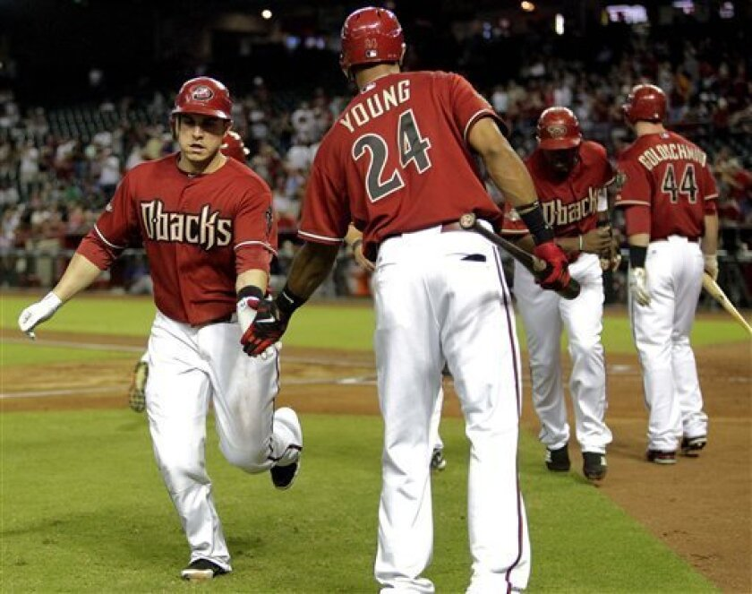 Arizona Diamondbacks' Miguel Montero, left, is greeted by teammate Chris Young (24) after hitting a three-run home run against the Colorado Rockies during the first inning of a baseball game, Wednesday, Aug. 31, 2011, in Phoenix. At right are Diamondbacks' Justin Upton and Paul Golschmidt (44). (AP Photo/Matt York)