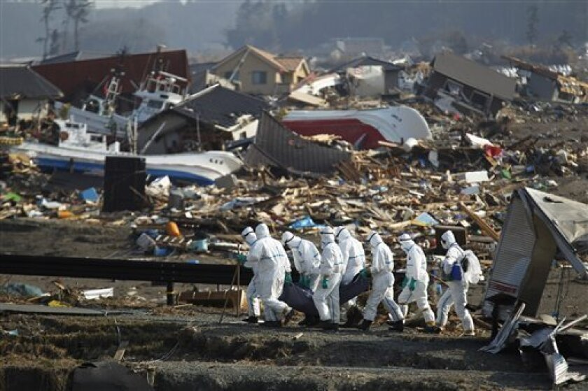 FILE - In this April 15, 2011 file photo, Japanese police officers carry a body during a search and recovery operation for missing victims in the area devastated by the March 11 earthquake and tsunami in Namie near the tsunami-crippled Fukushima Dai-ichi nuclear power plant in Fukushima Prefecture, northeastern Japan. Japanese nuclear regulators trusted that the reactors at Fukushima Dai-ichi were safe from the worst waves an earthquake could muster based on a single-page memo from the plant operator nearly a decade ago. The towering waves unleashed by the magnitude-9.0 earthquake on March 11 destroyed backup generators for several reactors' cooling systems, and the nuclear cores in three reactors melted, sparking the worst atomic crisis the world since Chernobyl. Workers have yet to bring the plant under control more than two months later. (AP Photo/Hiro Komae, File)