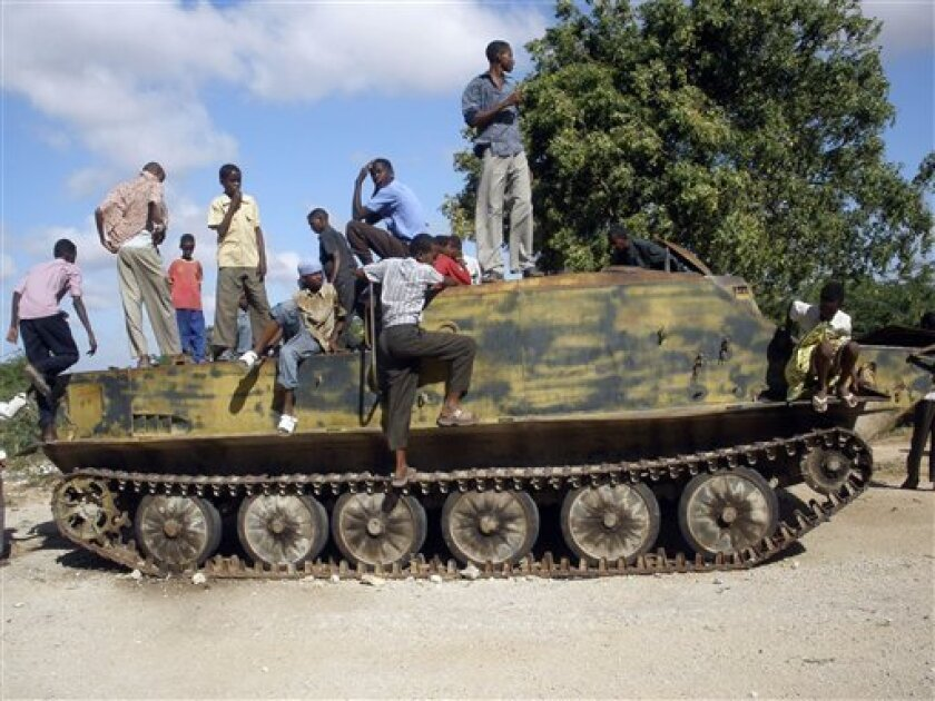 Somalis gather around a tank left by Ethiopian troops formerly based in the former Somali defence ministry in Mogadishu Thursday, Jan.15, 2009 . The Somali government called in the Ethiopians two years ago to oust an umbrella Islamic group that had controlled southern Somalia and the capital for si