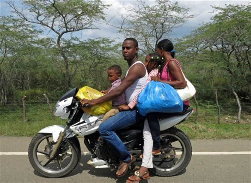In this July 15, 2013 photo, a family of four travel on a motorcycle on the road between Dajabon and Montecristi, Dominican Republic. The Dominican Republic is effectively the deadliest nation anywhere for drivers, second only to the tiny South Pacific island of Niue, where each death among its roughly 1,400 inhabitants spikes the fatality average. For every 100,000 inhabitants in the Dominican Republic, 42 die every year from traffic accidents, according to the World Health Organization. (AP Ph