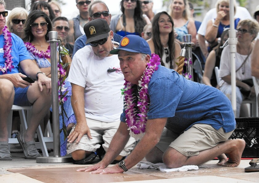 John Davis, who in 1967 was the first captain of the Huntington Beach High School surfing team, imprints his hands in wet cement as he is inducted into the Surfers' Hall of Fame on Friday in Huntington Beach.