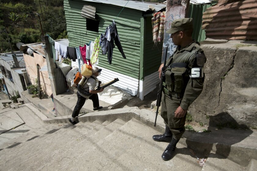 In this Feb. 5, 2016 photo, a soldier provides security for a Health Ministry worker fumigating against the Aedes aegypti mosquito in the La Comuna 2 neighborhood of Guatemala City. For health workers battling Zika across much of Central America, the immediate menace is not the mosquitoes that tran