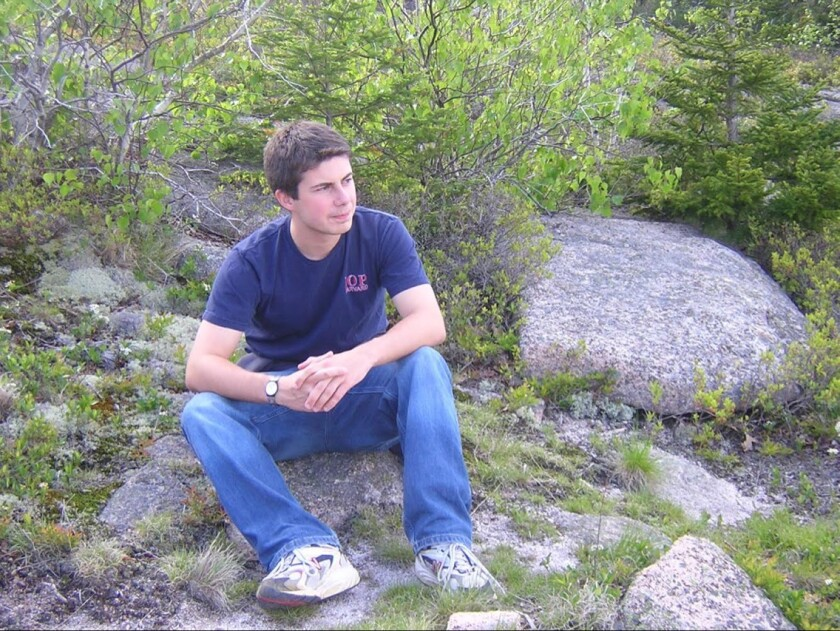 A young person sits on a rock.