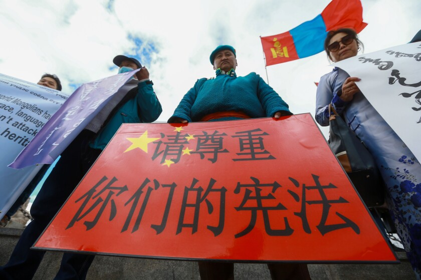 """A Mongolian man holds a protest banner in the shape of the Chinese flag which reads """"Respect your constitution"""" during a protest against China's plan to introduce Mandarin-only classes at schools in the Chinese province of Inner Mongolia, at Sukhbaatar Square in Ulaanbaatar, the capital of Mongolia on September 15, 2020. - Protests greeted Chinese Foreign Minister Wang Yi on a visit to Ulaanbator on September 15, with around a hundred Mongolians gathered in the city's main square to speak out against the Chinese government and its new language policy. (Photo by BYAMBASUREN BYAMBA-OCHIR / AFP) (Photo by BYAMBASUREN BYAMBA-OCHIR/AFP via Getty Images)"""