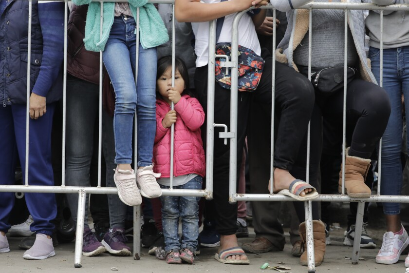 A child stands behind a barricade as supporters of Presidential candidate Keiko Fujimori watch her arrive to cast her vote in Lima, Peru, Sunday, June 6, 2021. Peruvians head to the polls in a presidential run-off election to choose between Fujimori, the daughter of jailed ex-President Alberto Fujimori, and political novice Pedro Castillo. (AP Photo/Guadalupe Pardo)