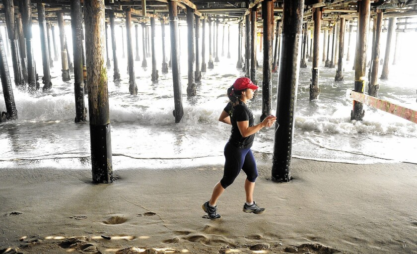 A jogger runs past the Santa Monica Pier. After an absence of four years, the popular beach at the pier has rejoined the list of Heal the Bay's 10 most polluted beaches statewide.