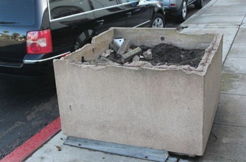 Some of the planter boxes on Girard Avenue have been broken or cluttered with trash and debris. File
