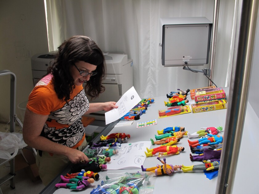 Editor Nina Wiener prepares DC action figures for a photo shoot for 75 Years of DC Comics, 2010. Cre