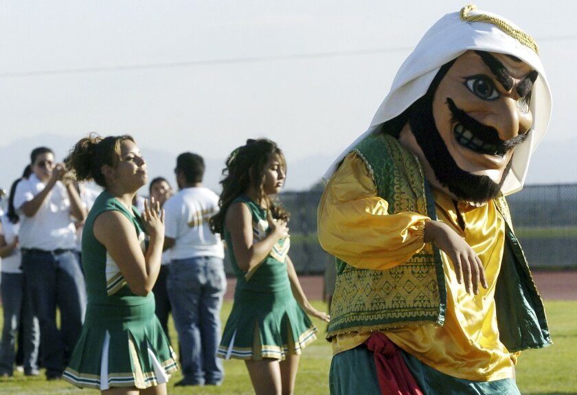 """FILE - In this Nov. 10, 2005, file photo, Coachella Valley High School's mascot, """"Arab,"""" dances to the band during a pep rally at the school in Thermal, Calif. The hook-nosed, snarling mascot who wears a head scarf did not appear at Coachella Valley High School's season opening football game Friday, Aug. 29, 2014. A belly-dancing genie that often appears with the mascot was also retired. The Desert Sun reports the change among the steps the Coachella Valley Unified School District is taking to give the mascot a makeover. (AP Photo/The Desert Sun, Marilyn Chung, File) RIVERSIDE PRESS-ENTERPRISE OUT; NO SALES; NO FOREIGN"""