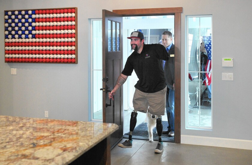 Marine Sgt. Nick Kimmel, whose legs and arm were amputated after he was wounded in Afghanistan, enters his new home in Fallbrook. The custom smart home has wide hallways, lowered countertops and window blinds controlled via iPad.