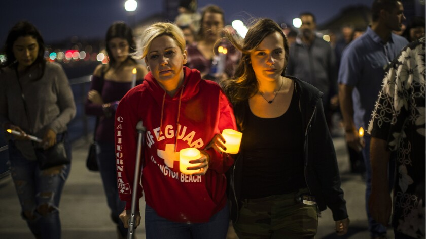 Walking with a crutch, shooting victim Tiffany Katsaris,45, of Huntington Beach, left, walks arm-in-arm with her daughter Tara Handshaw, right, during a candlelight procession on the Huntington Beach Pier.