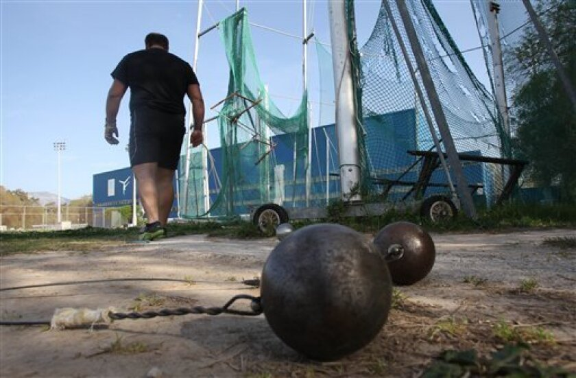 In this photo taken Tuesday, April 3, 2012, a hammer thrower leaves a training area at the Agios Cosmas sports facilities in southern Athens. The head of Greece's athletics federation said Tuesday that the body is considering suspending its operations due to deep cuts in state funding over the past two years in the crisis-hit country. (AP Photo/Thanassis Stavrakis)