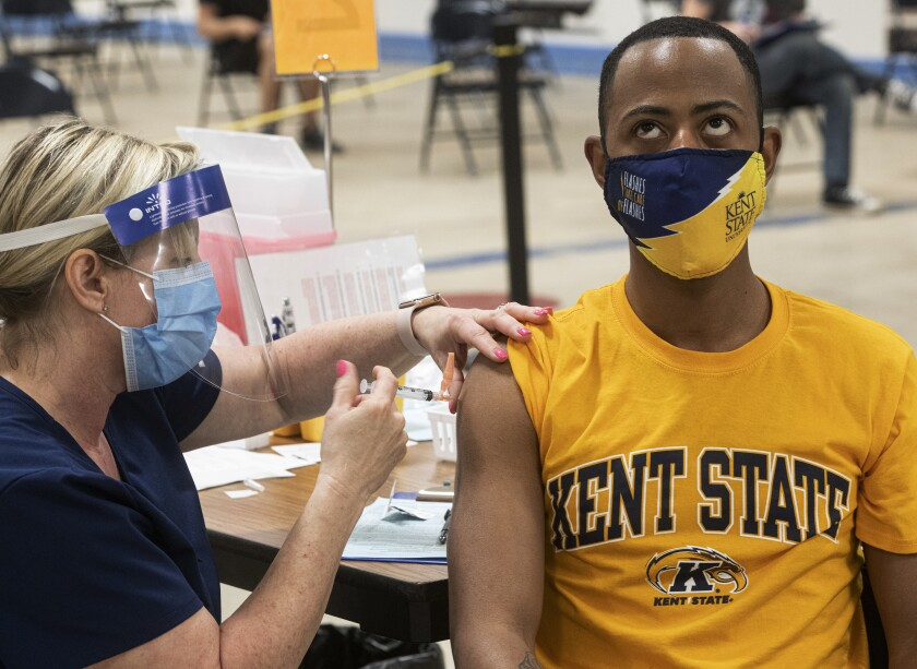 A Kent State University student bares his arm for a COVID-19 vaccination.