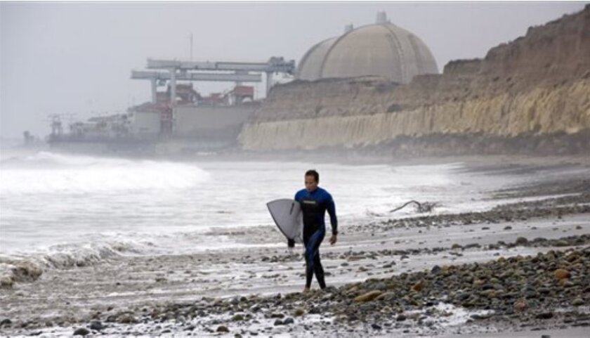 With the San Onofre Nuclear Generating Station as a backdrop, Huy Pham of San Juan Capistrano walks south along the beach at San Onofre State Beach early Friday morning, June 7, 2013, after it was announced that the nuclear plant will be closing permanently.