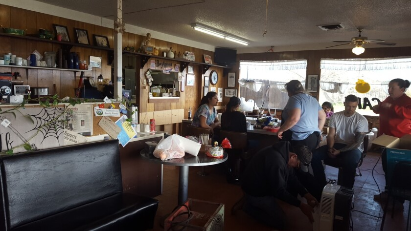 Community members gather Wednesday to help repair Kim's Country Cafe, which was damaged by floodwaters over the weekend.