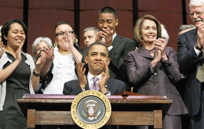 President Obama and others applaud after he signed the Health Care and Education Reconciliation Act of 2010.