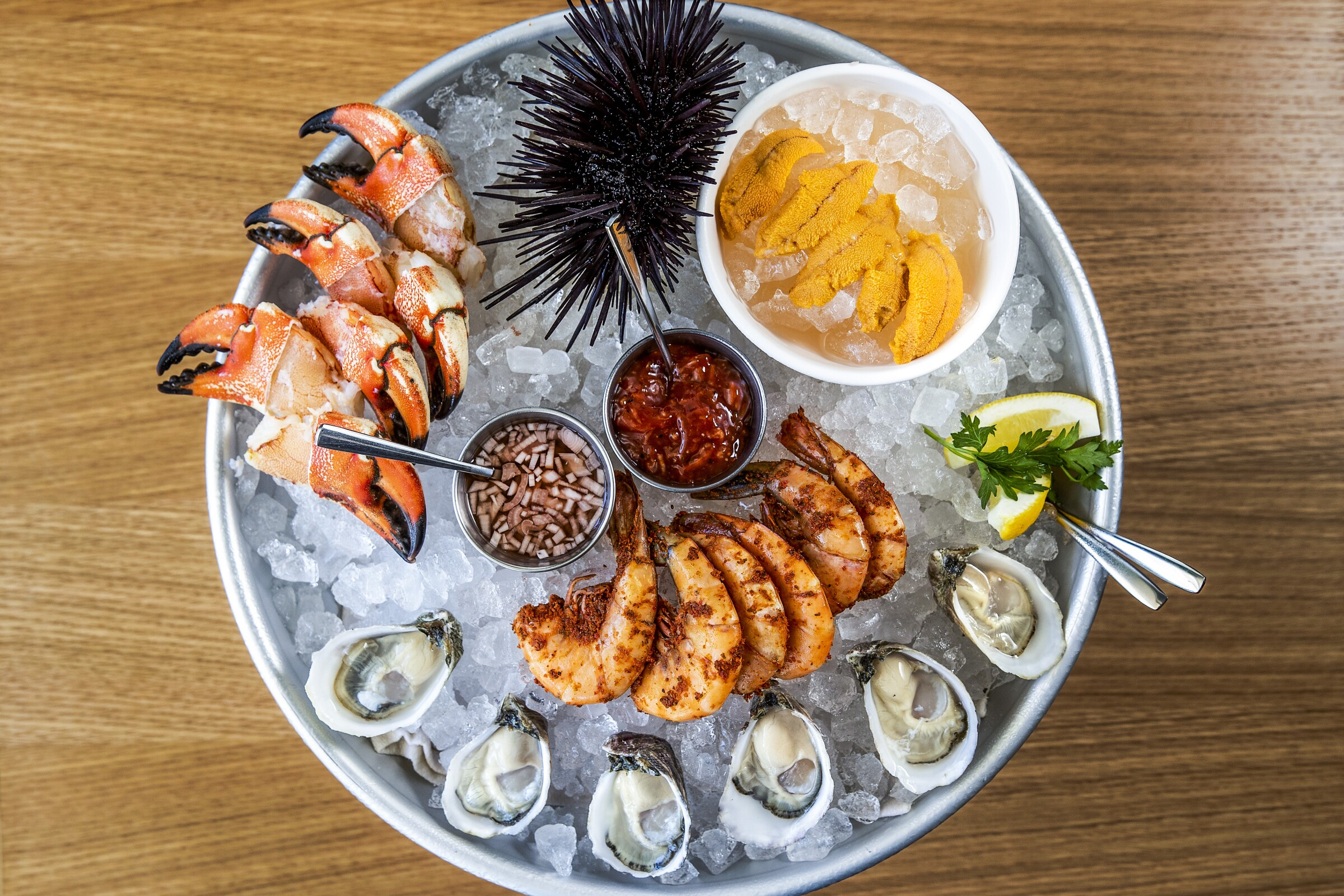 Jonah crab claws, Santa Barbara sea urchin, peel-and-eat shrimp and Pacific Gold Reserves oysters on ice.