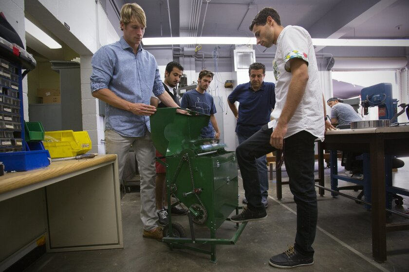 SDSU business student Peter Morrill (left), project manager for the thresher that was created by mechanical engineering students for Ethiopian farmers, assists Alejandro Davila (right) in demonstrating a prototype of the machine. Davila, along with Nader Alshanneri, Dominick Polese and Mohammad Bri