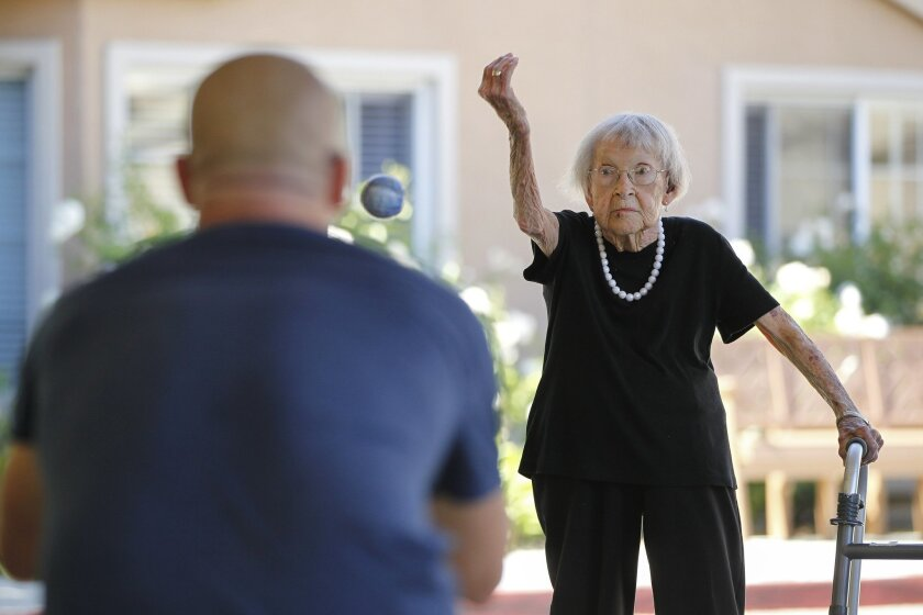 Agnes McKee practiced her pitching Thursday with Thomas Fraser, a staff member at the Fairwinds -- Ivey Ranch Retirement Community in Oceanside. / photo by Hayne Palmour IV * U-T San Diego