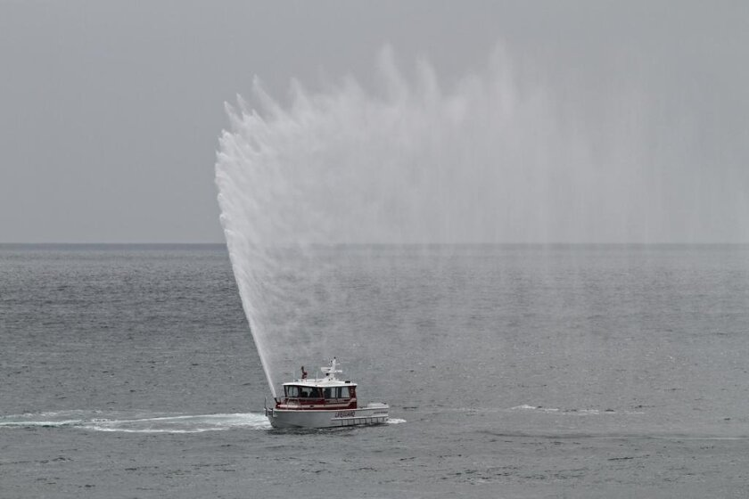 A lifeguard vessel shoots its water cannon to send off one of its beloved members, Mark Feighan.