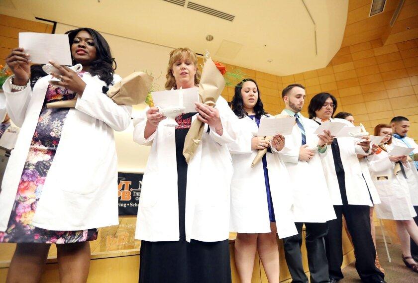 Graduating nursing students recite the Nightingale Pledge during a ceremony in 2015.