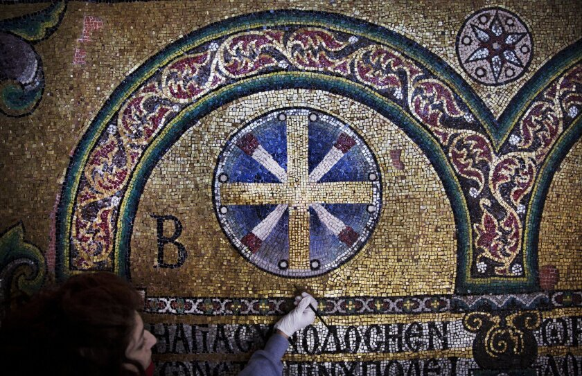 In this Feb. 4, 2016 photo, a restoration expert works on a mosaic inside the Church of the Nativity, in the West Bank city of Bethlehem. After two years of painstaking work, experts have completed the initial phase of a delicate restoration project at the Church of the Nativity, giving a much-need