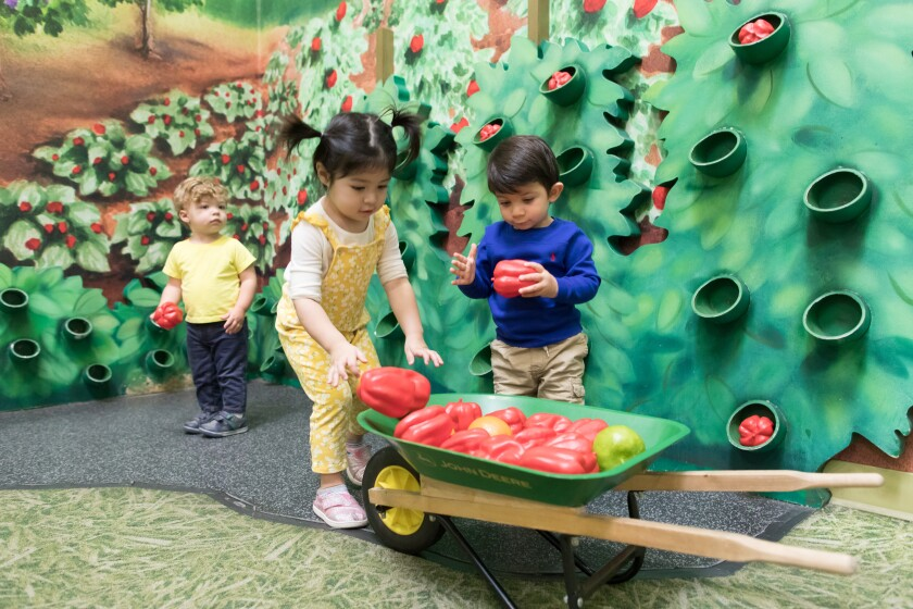 Kids at Pretend City Children's Museum play in their interactive farm exhibit, where they can plant seeds and pick fruit.