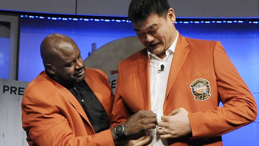 Shaquille O'Neal helps Yao Ming with his jacket during a news conference at the Basketball Hall of Fame on Thursday.