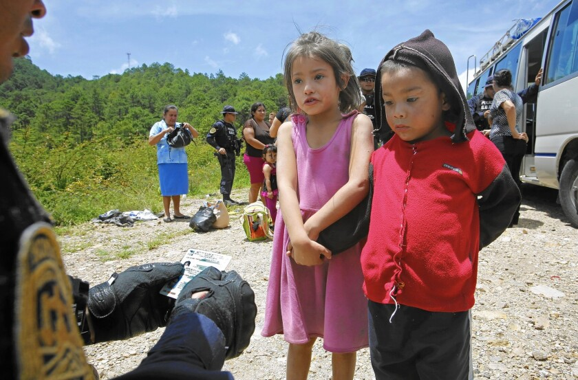 Two siblings in Ocotepeque, Honduras, speak to an official whose questions were designed to evaluate whether children were being smuggled to the U.S. as part of a summer wave of illegal immigration.