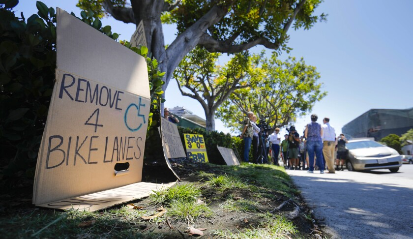 A poster that reads remove handicap parking for bike lanes sits on the sidewalk where a group of opponents of a San Diego plan to remove more than 400 parking spaces in North Park hold a news conference on Tuesday.