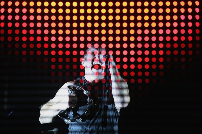 Trent Reznor leads his band Nine Inch Nails from behind a scrim of flashing lights at Staples Center on Friday.
