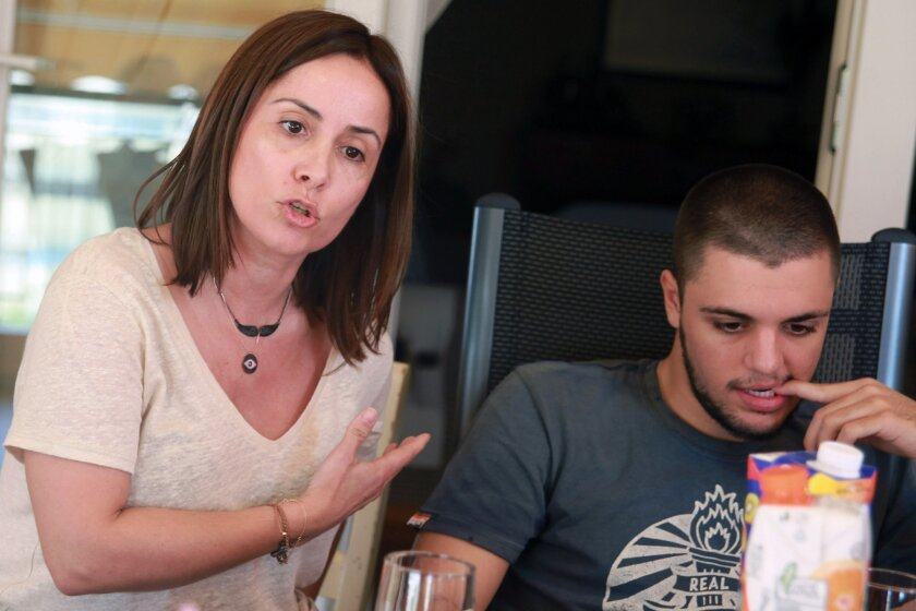 Dimitra Danikoglou, 48, gestures as she talks next to her son Nikolas, 23, at their apartment in Athens, Saturday, July 4, 2015. Meet the Danikoglous, a typically intense, articulate Greek family divided over how best to cope with Greece's careening financial crisis, which may lead to a break with