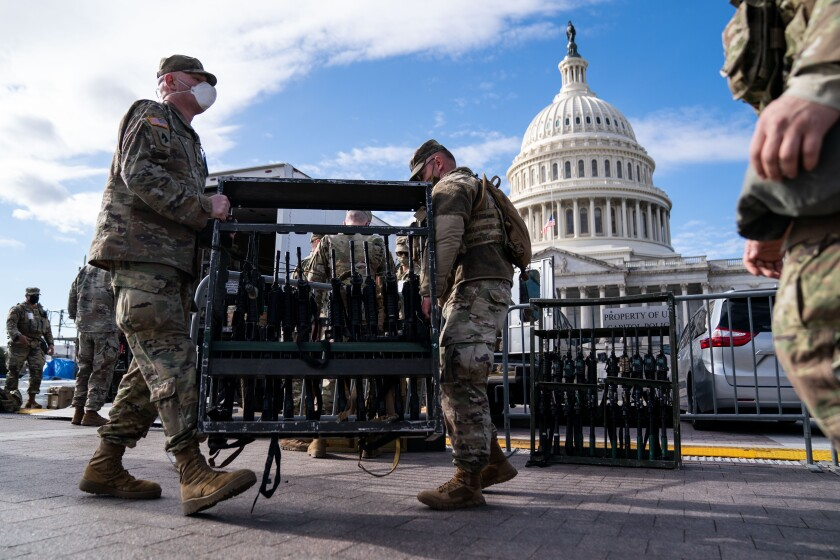 National Guard members unload weapons and supplies outside of the U.S. Capitol building.