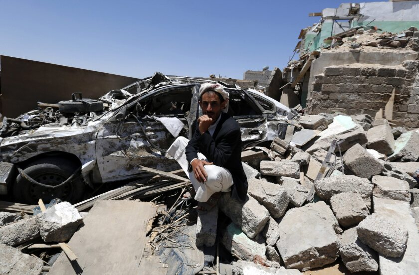 A Yemeni man sits beside his car and over the rubble of his house that was allegedly destroyed by an airstrike of the Saudi-led coalition targeting Houthi rebel positions in Sana, Yemen, on March 28.
