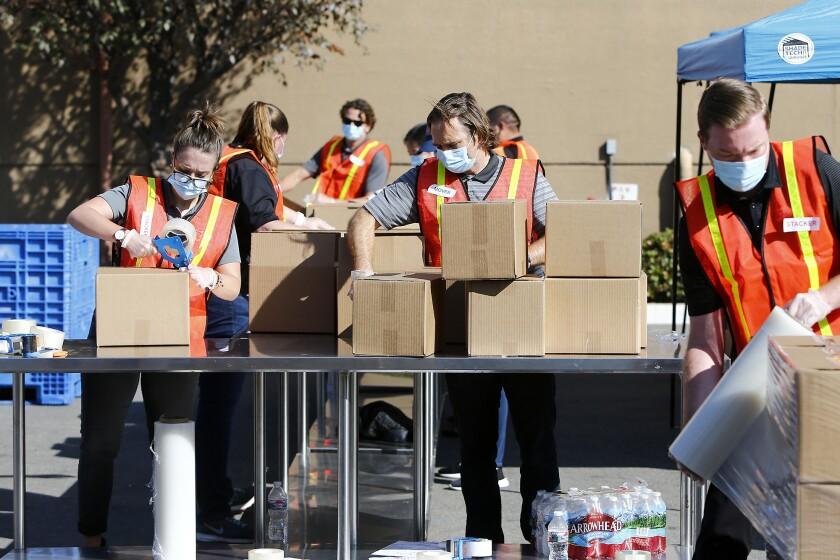 Volunteers package boxed Thanksgiving meals