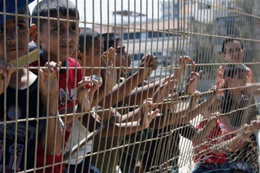 Palestinian boys stare through a fence in Gaza port, as they await a flotilla of aid ships which leaves today for the blockaded territory, in Gaza city, Sunday, May 30, 2010. Hundreds of pro-Palestinian activists on seven ships were to set sail for the Gaza Strip on Sunday from international waters