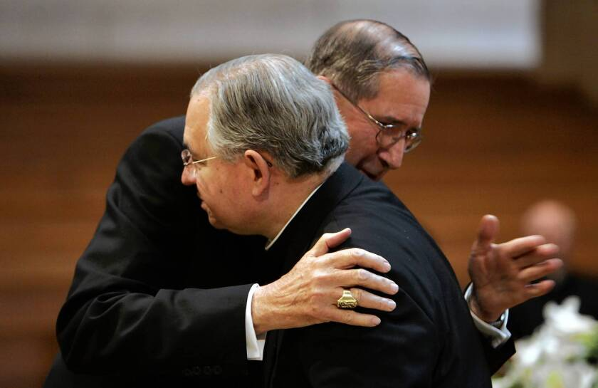 Cardinal Roger Mahony, left, hugs Archbishop Jose Gomez in 2010, the year before Gomez succeeded Mahony as head of the Los Angeles Archdiocese.
