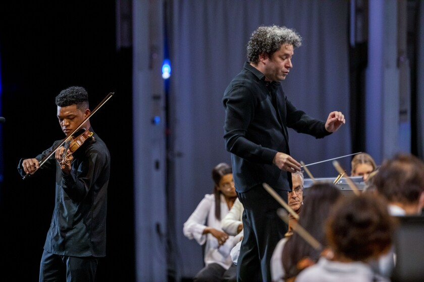 A standing violinist performs as a conductor leads a seated orchestra