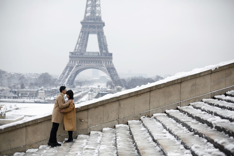 Una pareja de turistas se besa frente a la Torre Eiffel, cerrada por mal clima. Los visitantes tuvieron que conformarse con ver la torre de hierro blanqueada por nieve desde los jardines cercanos al monumento en París.