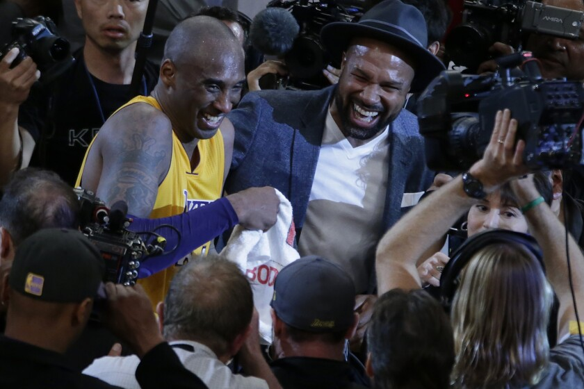Kobe Bryant shares a laugh with former teammate Derek Fisher on the court after scoring 60 points in his last game as a Laker at Staples Center.